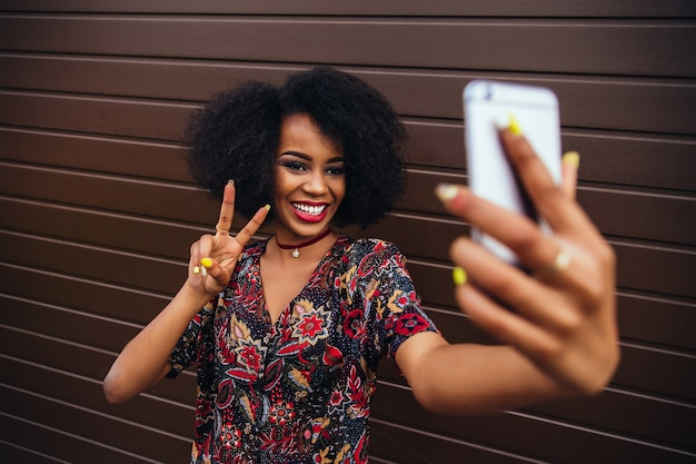 Young afro-american girl showing a peace sign while taking a selfie on mobile phone.