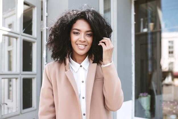 베이지 색 코트와 흰 셔츠에 서있는 검은 곱슬 머리를 가진 젊은 아프리카 계 미국인 소녀 아름다운 웃는 아가씨
