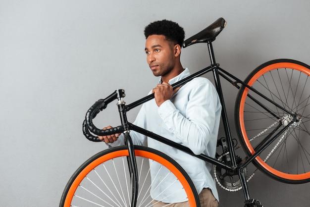 自転車を運ぶ若いアフロアメリカンの男
