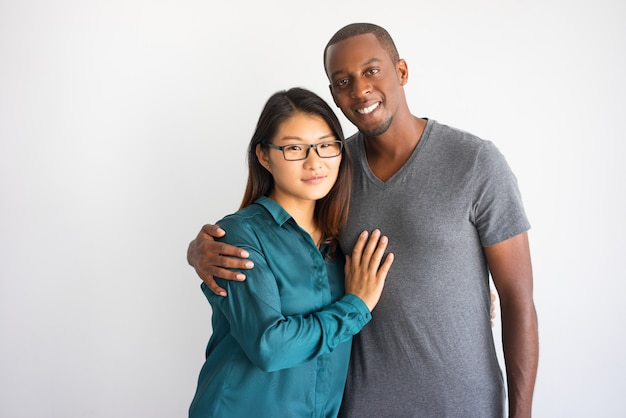 Young afro american man hugging his asian girlfriend with glasses.