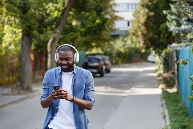 音楽アプリを使用してスマートフォンで音楽を聴いているヘッドフォンで若いアフリカ系アメリカ人の男