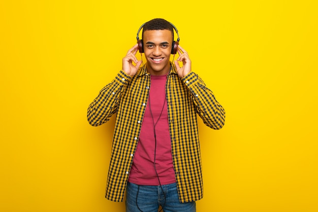 Young afro american man on listening to music with headphones