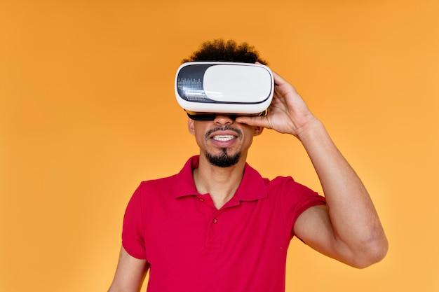 Giovane uomo afroamericano in posa sulla parete arancione che indossa abiti estivi e indossa le cuffie da realtà virtuale