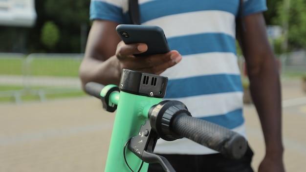 젊은 아프리카계 미국인 남자는 휴대폰 앱을 사용하여 전기 스쿠터를 임대합니다. 남자는 스마트폰을 닫고 전기 스쿠터를 잠금 해제했습니다