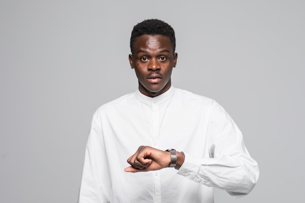 Young afro american man in shirt look at hand watch isolated on gray background