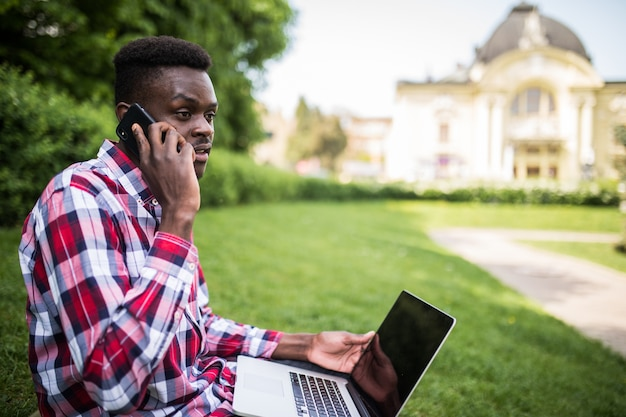 Young afro american man speak on the phone while sitting on the green grass with laptop on city street