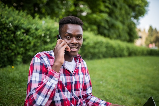 Young afro american man speak on the phone while sitting on the green grass with laptop