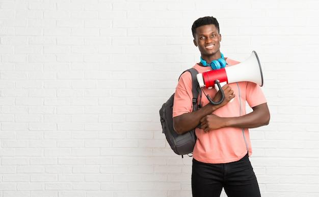メガホンを持つ若いアフロアメリカ人の男子学生