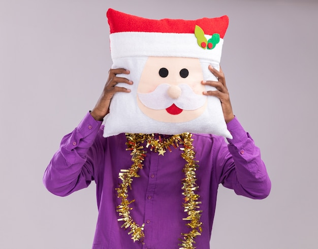 Young afro-american man wearing glasses with tinsel garland around neck holding santa claus pillow in front of face isolated on white background