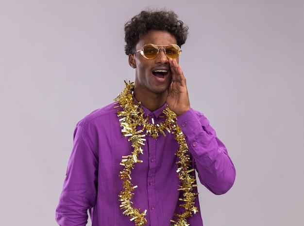 Giovane uomo afro-americano con gli occhiali con la ghirlanda di orpelli intorno al collo guardando la telecamera sussurrando isolati su sfondo bianco