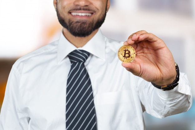 Young afro american man with bitcoin in hand