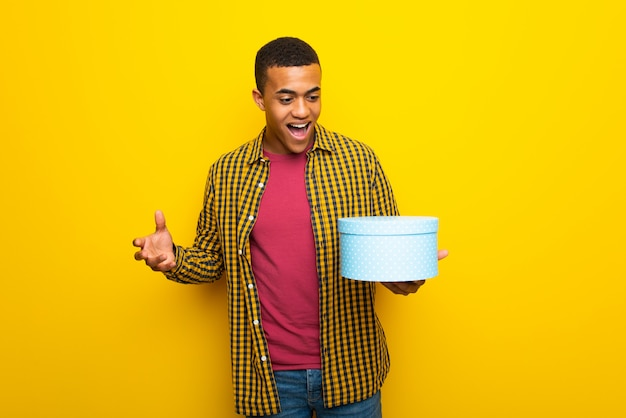 Young afro american man on yellow background holding gift box in hands