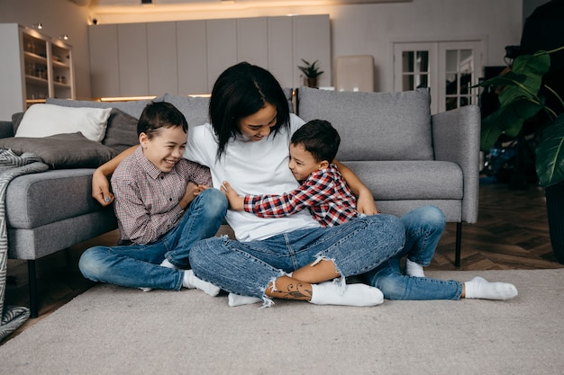 Young afro american mom hugs her beloved little children tenderly Premium Photo
