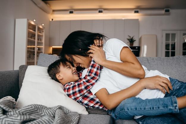 젊은 아프리카 계 미국인 엄마는 사랑하는 아들을 부드럽게 안아줍니다. 고품질 사진