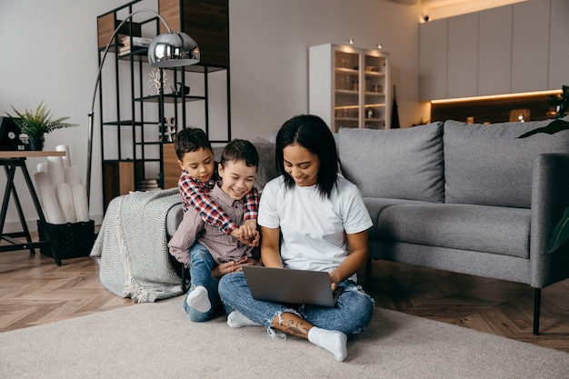 Young afro american mom with two sons make video call by laptop with their daddy. remote family relationship concept. high quality photo