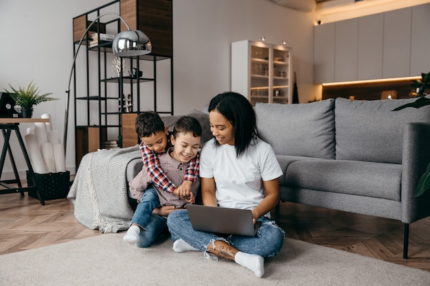 Young afro american mom with two sons make video call by laptop with their daddy. remote family relationship concept