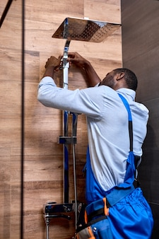 シャワー室の固定蛇口を修理する若いアフロアメリカの配管工の男、側面図の肖像画、シャワーを修理する青いオーバーオールの黒のプロの熟練した便利屋。サービス、組み立てコンセプト