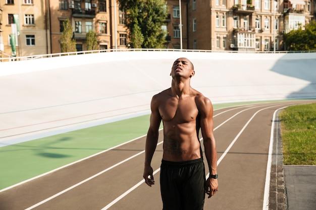 Молодой афроамериканский бегун отдыхает после соревнований на стадионе