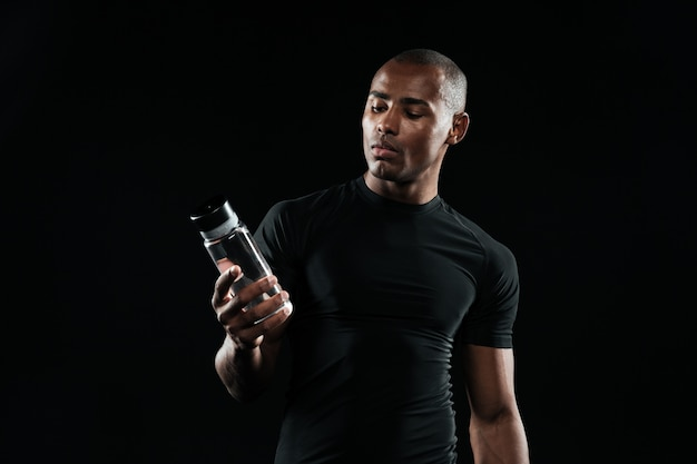 Young afro american sports man holding bottle of water