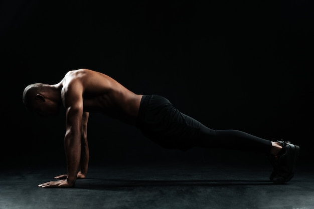 Young afro american sports man with beautiful muscular body doing pushup exercise