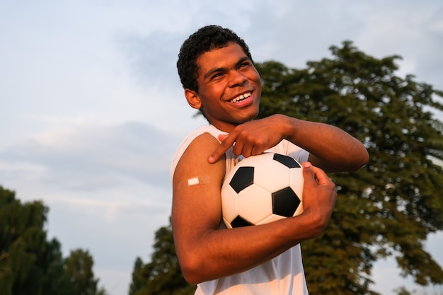 Young afro american sportsman showing his arm after receiving vaccine at sunset