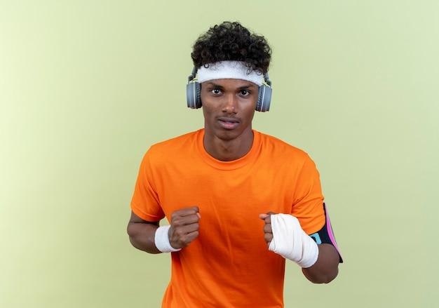 녹색 벽에 고립 된 포즈 싸움에 서있는 헤드폰으로 머리띠와 팔찌와 전화 팔 밴드를 착용하는 젊은 아프리카 계 미국인 스포티 한 남자