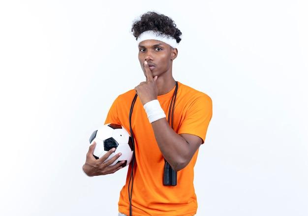 어깨에 점프 로프와 함께 침묵 제스처를 보여주는 공을 들고 머리띠와 팔찌를 착용하는 젊은 아프리카 계 미국인 스포티 한 남자