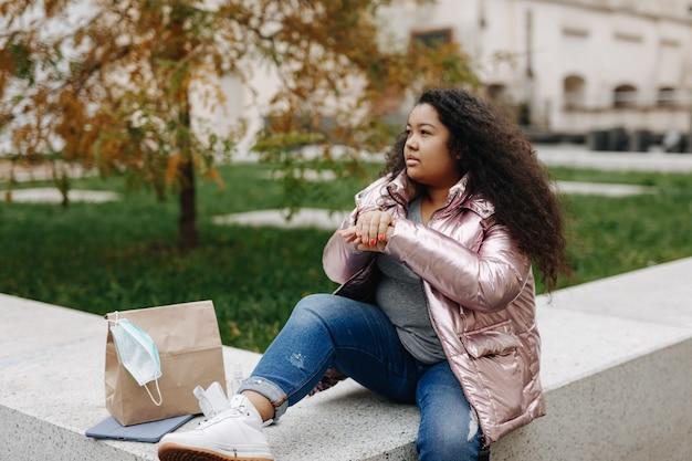 暖かい服を着て屋外に座って、手に消毒剤を使用している若いアフリカ系アメリカ人の女性。エピデミックの発生の防止。