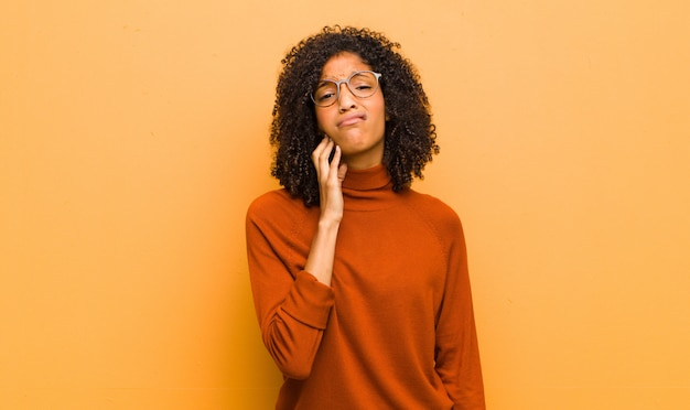 Young afro-american woman posing while being undecided