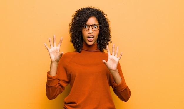 Молодая афроамериканка позирует с испуганными и удивленными чувствами