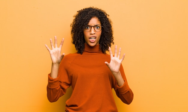 Young afro-american woman posing while showing scared and surprised feelings