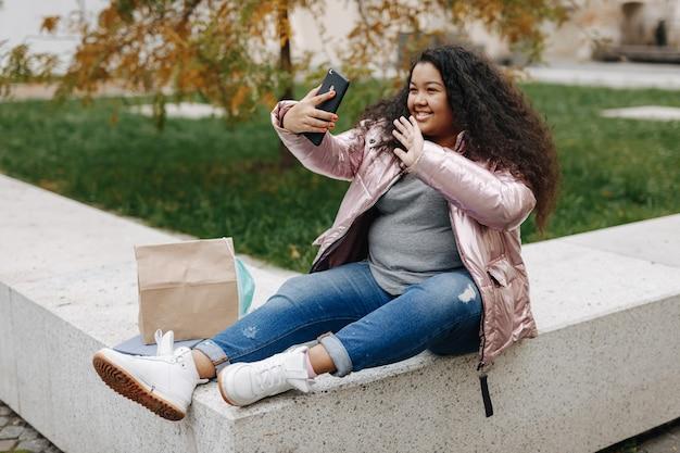 携帯電話でのビデオ通話中に笑顔で身振りで示す若いアフリカ系アメリカ人女性。屋外でオンライン会話をしている医療マスクのきれいな女性。