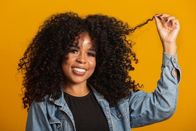 Молодая афроамериканская женщина с вьющимися волосами и улыбкой.