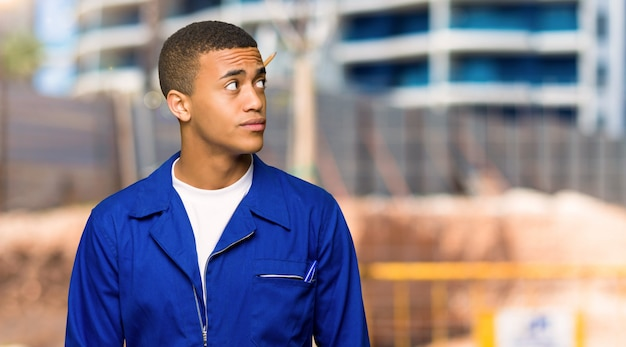 Young afro american worker man looking up with serious face in a construction site