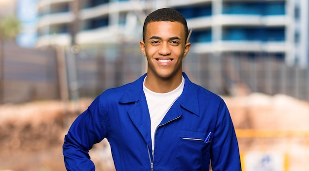 Young afro american worker man posing with arms at hip and smiling in a construction site