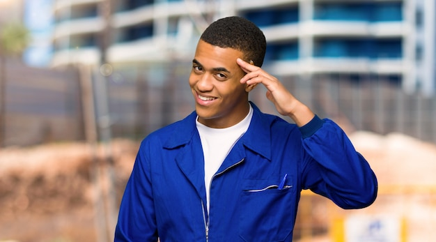 Young afro american worker man saluting with hand in a construction site