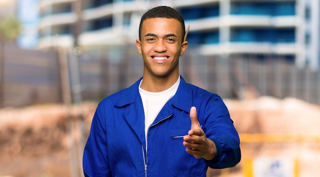 Young afro american worker man shaking hands for closing a good deal in a construction site