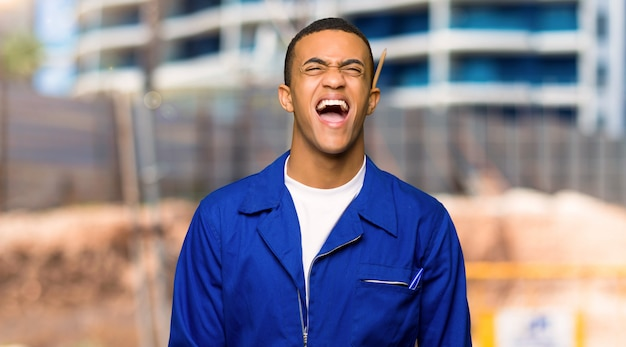 Young afro american worker man shouting to the front with mouth wide open in a construction site