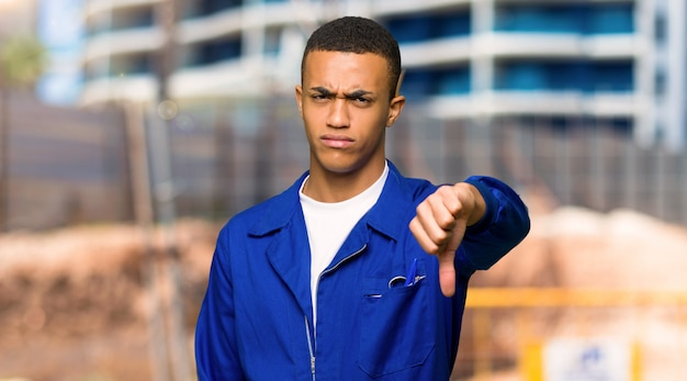 Young afro american worker man showing thumb down sign with negative expression