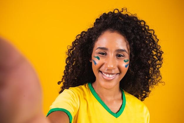 ブラジルのゲームの準備ができて自分撮りを作る若いアフリカ系ブラジル人のファン