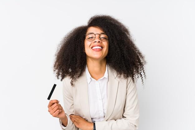 クレジットカーを持って孤立した若いアフロビジネスウーマンクレジットカーを持って笑って楽しんでいる若いアフロビジネスウーマン。