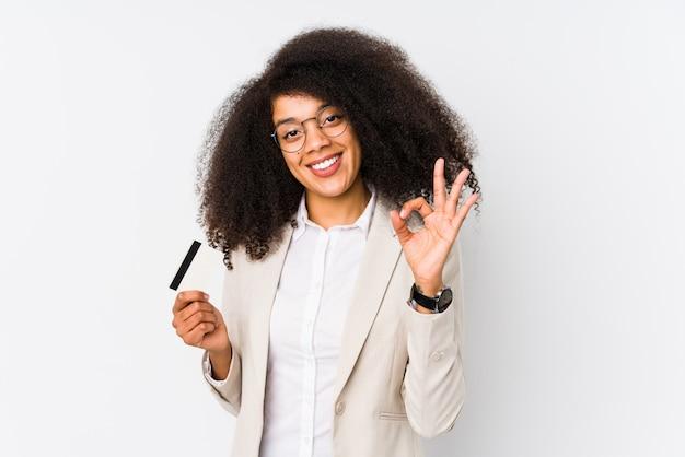 Молодая афро бизнес женщина, держащая кредитной карты, веселый и уверенный, показывая ок жест.
