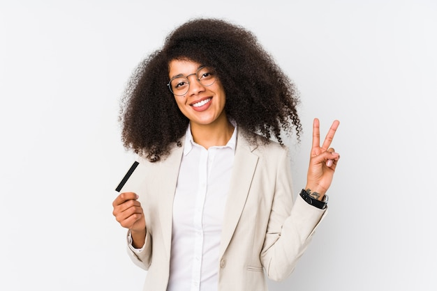 Young afro business woman holding a credit car isolated. young afro business woman holding a credit car joyful and carefree showing a peace symbol with fingers.