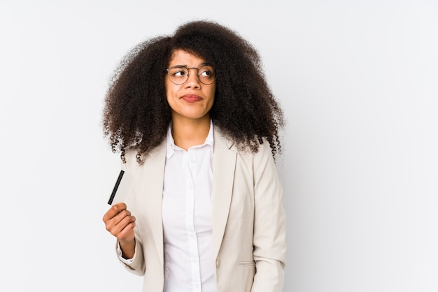 Young afro business woman holding a credit car isolated young afro business woman holding a credit carconfused, feels doubtful and unsure.