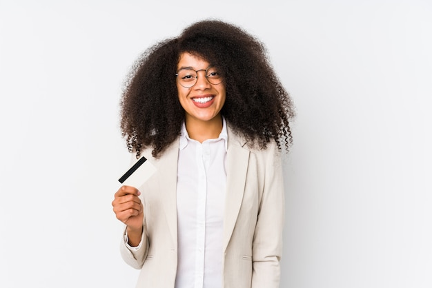 Young afro business woman holding a credit car isolated young afro business woman holding a credit carhappy, smiling and cheerful.
