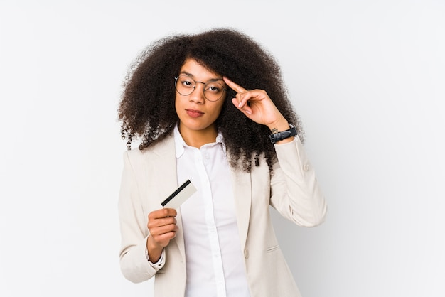 Young afro business woman holding a credit car isolated young afro business woman holding a credit carpointing temple with finger, thinking, focused on a task.