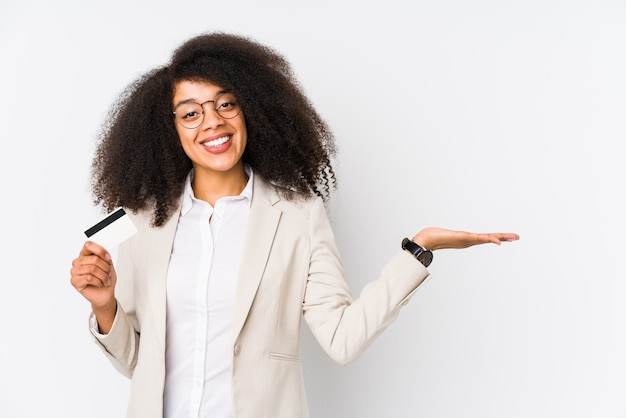Young afro business woman holding a credit car isolated young afro business woman holding a credit carshowing a copy space on a palm and holding another hand on waist.