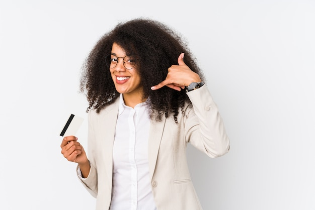 Young afro business woman holding a credit car isolated young afro business woman holding a credit carshowing a mobile phone call gesture with fingers.