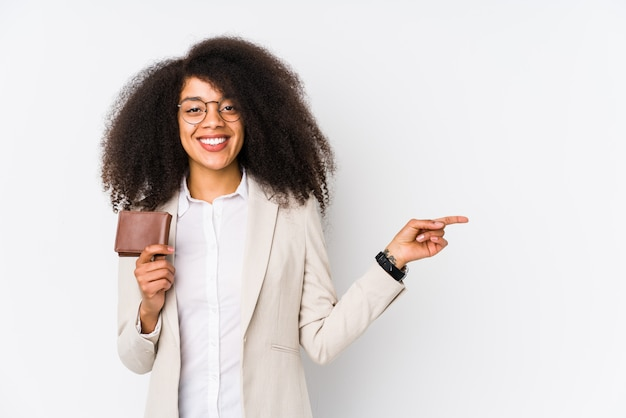 Young afro business woman holding a credit car isolated young afro business woman holding a credit carsmiling and pointing aside, showing something at blank space.