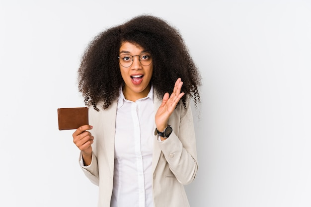 Young afro business woman holding a credit car isolated young afro business woman holding a credit carsurprised and shocked.